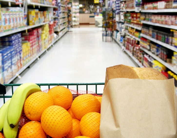 Grocery cart loaded with fresh fruit and bread moving through the aisle.