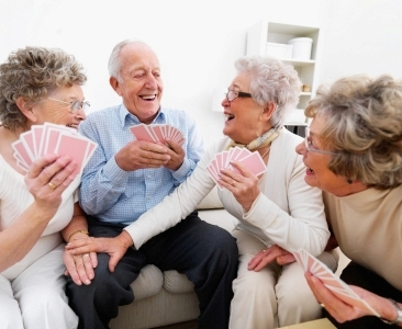 A group of happy elderly people enjoying themselves over a card game