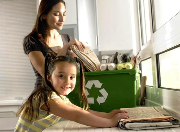 Girl (4-6) helping mother recycle newspapers, smiling, portrait
