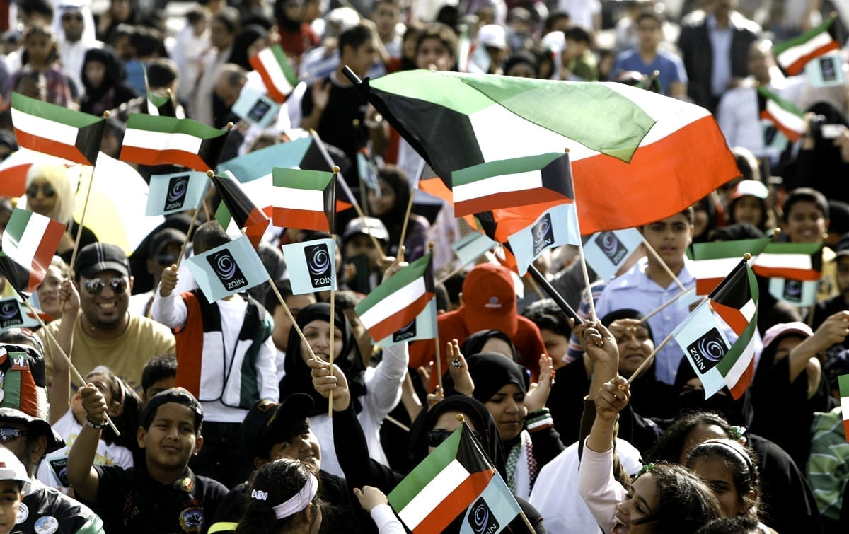 Kuwaitis wave their national flag during