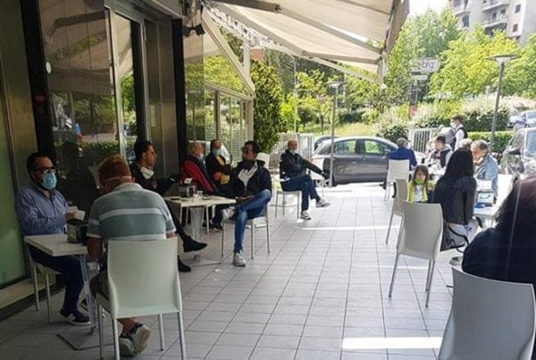 Clienti seduti ai tavoli di un bar consumano il loro caffè all aperto