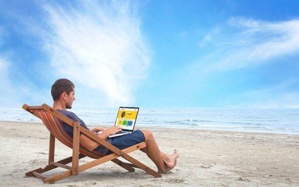 Un uomo lavora in spiaggia con il suo pc: sono le vacanze in smart-working