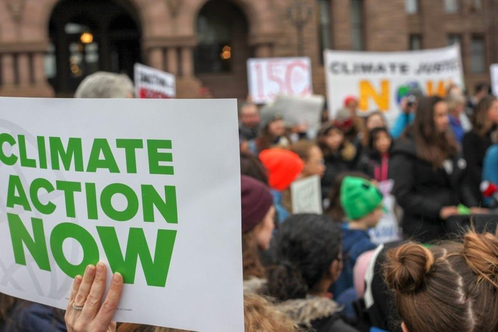 """Inquinamento atmosferico: ecco come rendere le città ecosostenibili. L'inquinamento atmosferico: le soluzioni per risolverlo, una volta per tutte. La foto ritrare una manifestazione ambientalista con un cartello in primo piano con scritto """"Climate action now"""""""