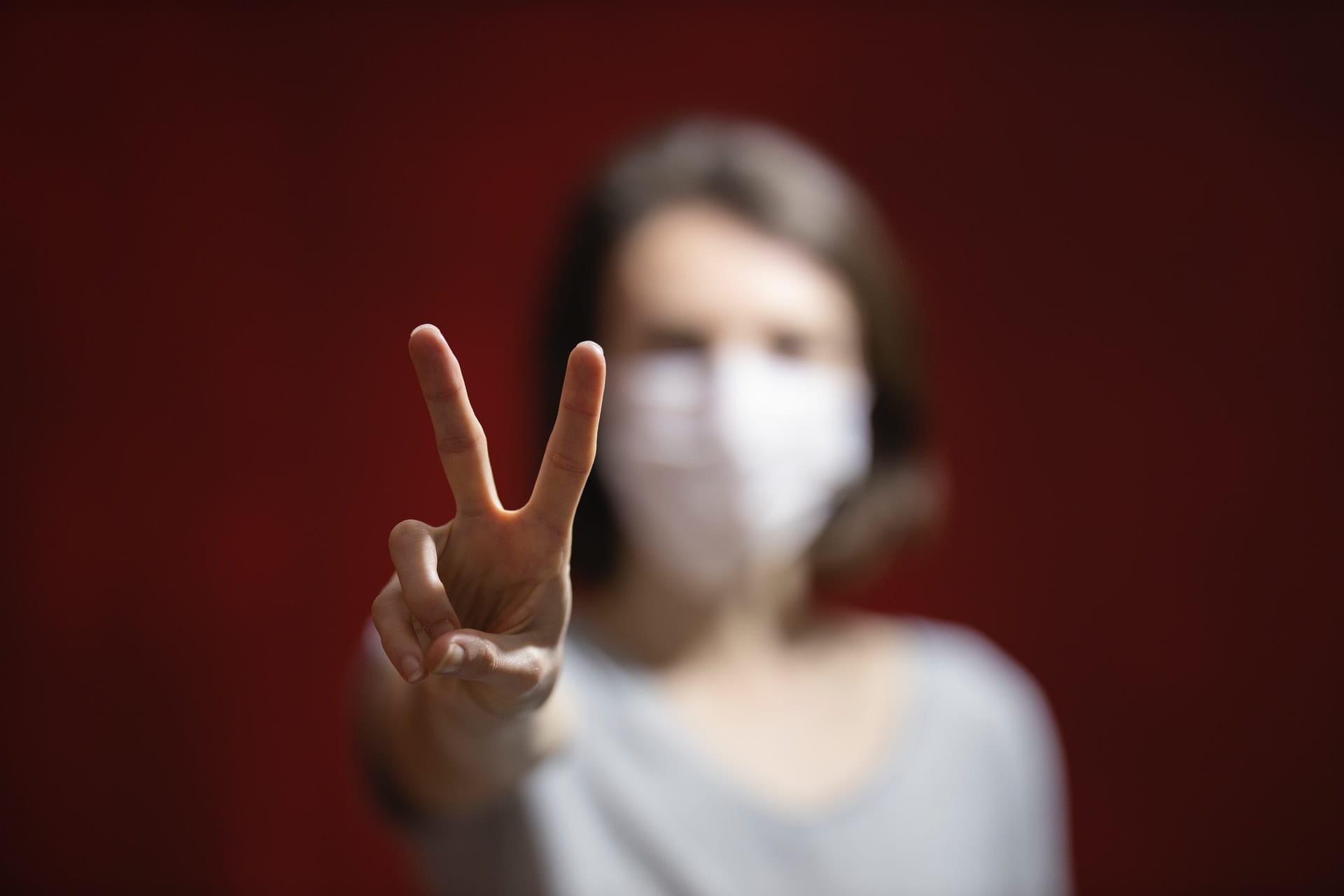 """Misure di contenimento del coronavirus: il modello vicente """"misto"""". Le misure di contenimento vincenti della Svizzera, dell'Islanda e della Lettonia per contrastare il contagio. La fotografia ritrae una donna, sfocata sullo sfondo, in cui è messo a fuoco la mano destra col simbolo della vittoria"""
