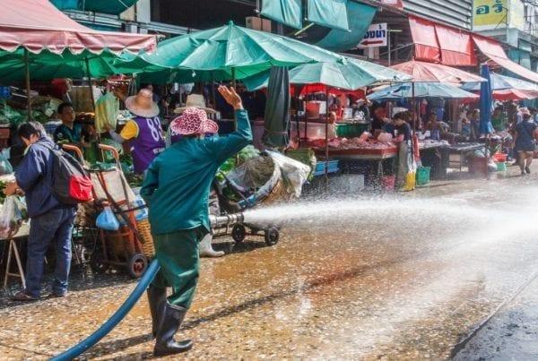 wet market: addetto pulisce con tubo dell'acqua la pavimentazione