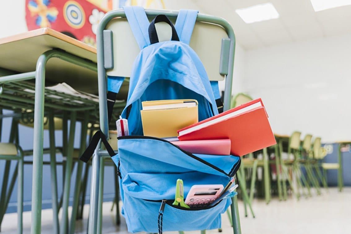 settembre a scuola: zaino aperto con libri, forbici e calcolatrice