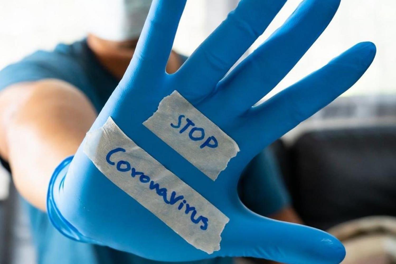 curva contagi: guanto blu con scritta STOP CORONAVIRUS
