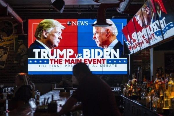 Elezioni USA 2020: chiunque vinca, l'America sarà sempre più green. Sia che vincano i Repubblicani che i Democratici, alle elezioni USA del 2020 l'America sarà sempre più verde. L'immagine raffigura l'attuale Presidente USA Donald Trump e il suo sfidante Joe Bidenraffigurati su un grande schermo all'interno di un pub